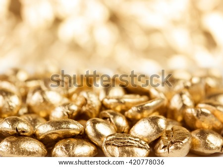 Gold coffee beans with unfocused background - stock photo