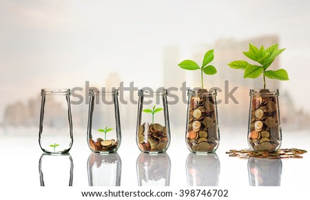 Gold coins and seed in clear bottle on cityscape photo blurred cityscape background,Business investment growth concept - stock photo