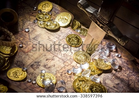 gold coins, diamonds, and a dagger on a treasure map - stock photo