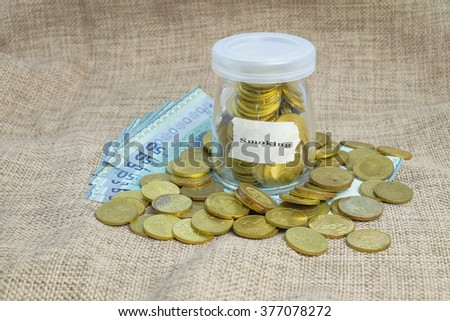 Gold coins in bottle  with word Smoking,Saving concepts - stock photo