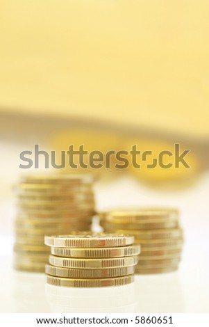 Gold coins in stacks, reflected against golden background.  Very shallow DOF. - stock photo