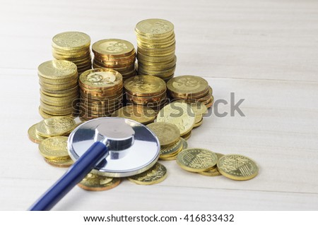 Gold coins stacked with stethoscope on the ground - Business Concept - stock photo