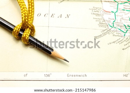 Gold color rope cable with simple knot and pencil put on old  and vintage paper map represent the detail of city name and destination.
