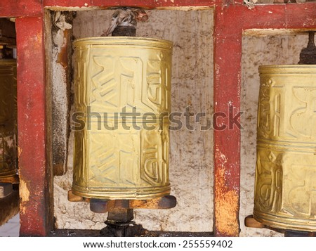 Gold colored Buddhist prayer wheel in the city center of Lhasa, Tibet - stock photo