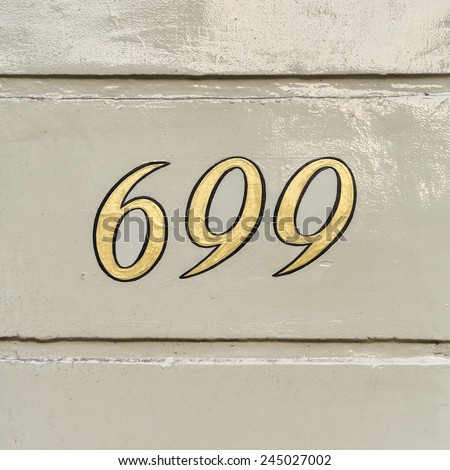 gold colored house number six hundred and ninety nine - stock photo