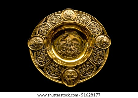 Gold communion plate depicting Matthew(angel), Mark (Lion), Luke (winged ox),John (eagle) and  grape vines surrounding a pelican feeding her young on blood (piety).  Norwich Cathedral, England. - stock photo