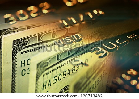 Gold credit card and one hundred dollars. Macro image - stock photo
