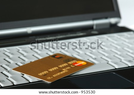 Gold Credit Card atop a Notebook - stock photo