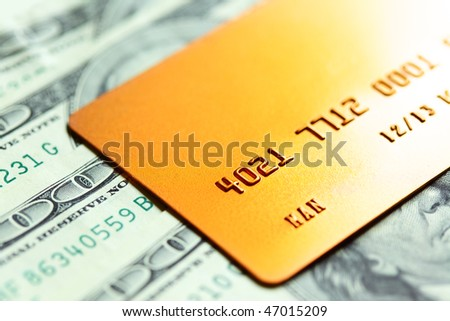 Gold credit card on dollar notes. Shalow DOF! - stock photo
