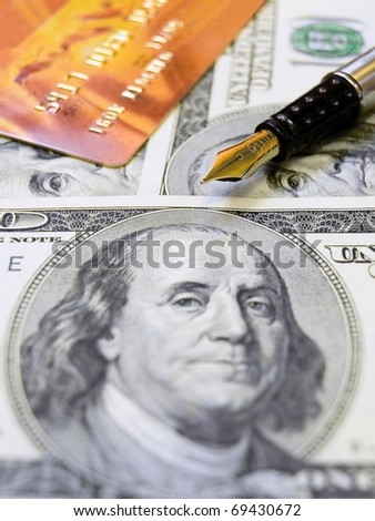 Gold credit card, us dollars and a pen - stock photo