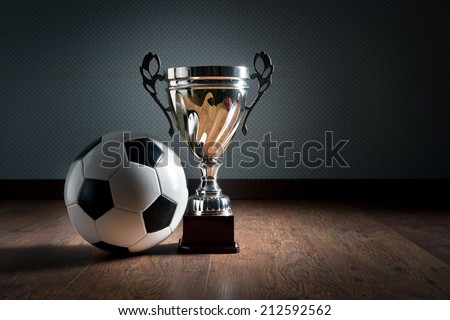 Gold cup trophy and soccer ball on hardwood floor, winning concept. - stock photo