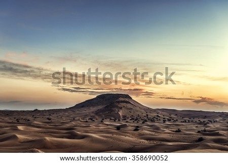 Gold desert in sunset. Middle East desert landscape with small dunes and colorful sky. Rock on background.  - stock photo