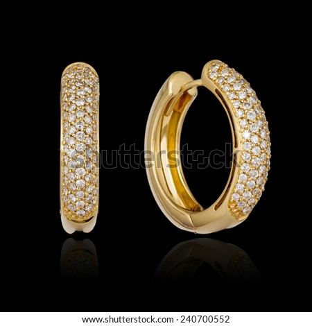 Gold diamond earrings isolated on black background - stock photo
