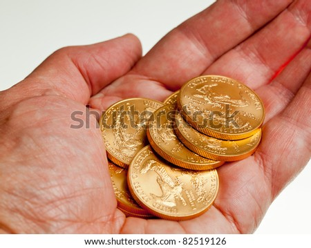 Gold Eagle one ounce coins in a stack in the palm of a hand - stock photo