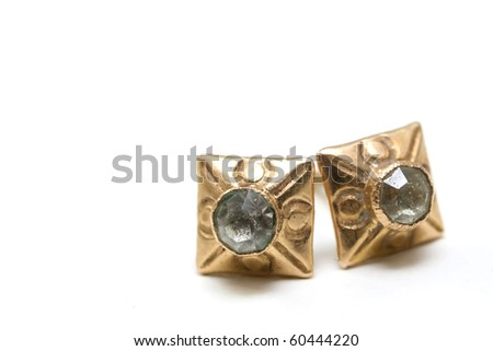 Gold earrings with diamonds over white background