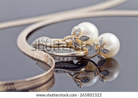 gold earrings with elements in the form of branches and leaves embellished with pearls - stock photo