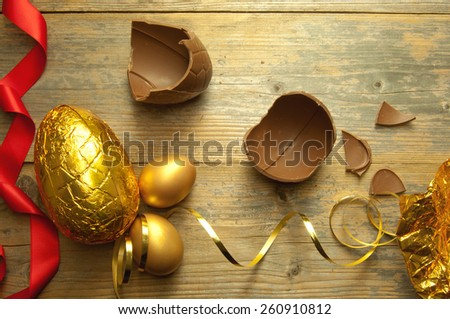Gold easter egg with broken chocolate pieces  - stock photo