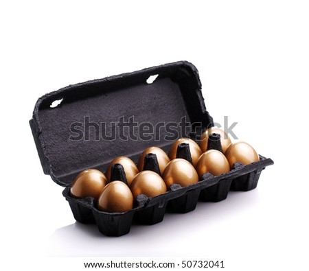 Gold eggs in a black carton on white background - stock photo