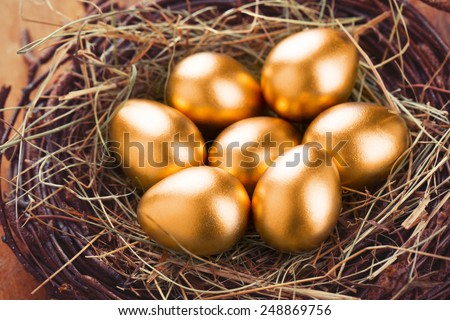Gold eggs in nest from hay on wood boards - stock photo