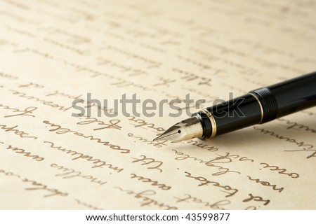 Gold Fountain Pen on Written Page. Crisp focus on nib of pen. - stock photo