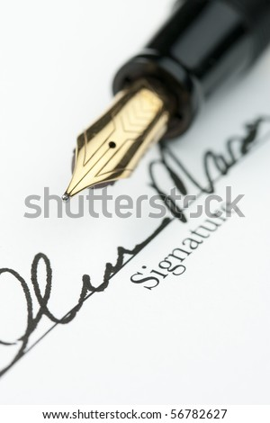 Gold fountain pen over obscured signature on document. Focus on tip of pen nib. - stock photo