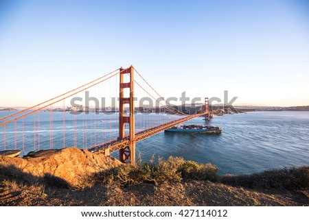 gold gate bridge and container ship on sea in blue sky