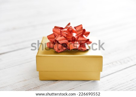 Gold gift box with red ribbon over white wooden background - stock photo