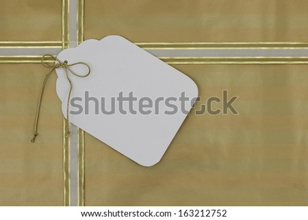 Gold gift wrapped package with large blank gift tag - stock photo