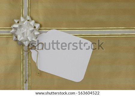 Gold gift wrapped package with large blank tag - stock photo