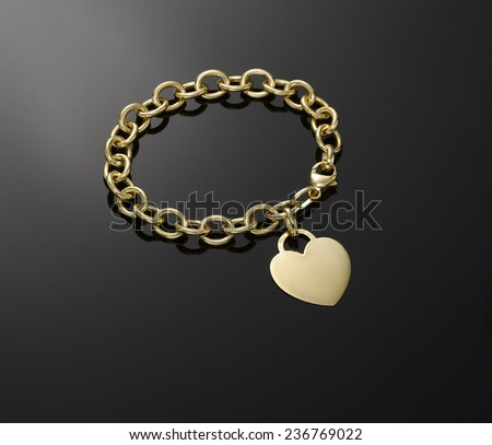 Gold heart pendant on gold chain link bracelet, shot on black background - stock photo