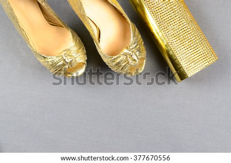 Gold high-heeled shoes and a clutch bag on a gray background. Top view - stock photo