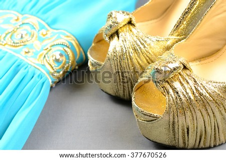 Gold high-heeled shoes, clutch bag and blue dress with gold accentson - stock photo