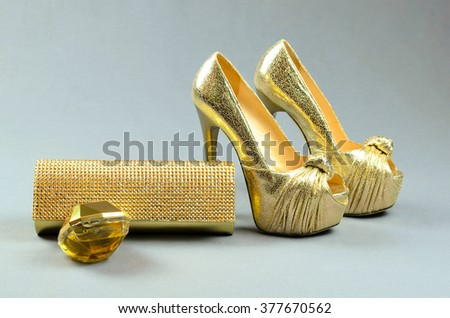 Gold high-heeled shoes, clutch bag and perfume on a gray background - stock photo