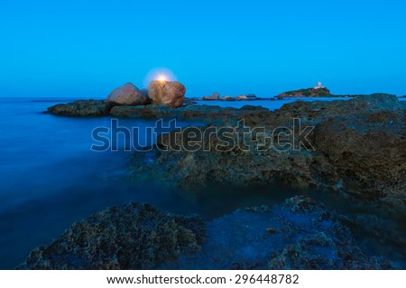 Gold hour over the wild rocky beach coastline and the sea. Lighthouse, moon and rocks at night wide angle view. Panoramic landscape in Sardegna, Nora place near Pula city.  - stock photo