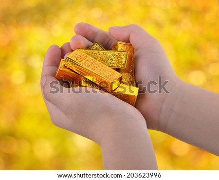 Gold ingots in the child's hand. - stock photo