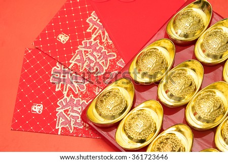 Gold ingots on red envelope of China in the Chinese New Year festive  - stock photo