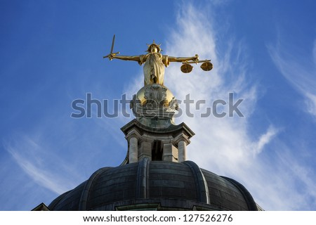 Gold Lady Justice Statue on the top of the Old Bailey in London, England. - stock photo