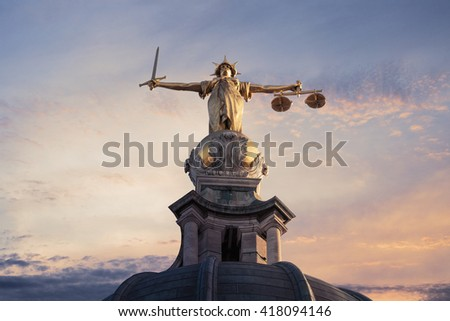 Gold Lady Justice Statue on the top of the Old Bailey in London, England, with a sunset sky in the background