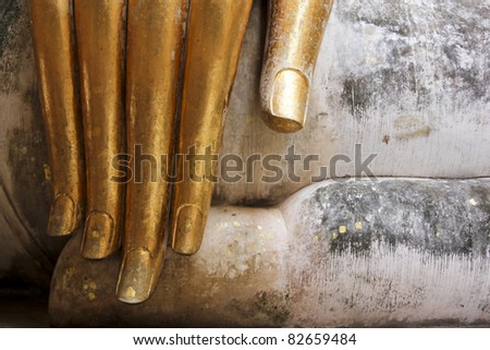 gold leaf offerings on slender fingers of wat si chums iconic big buddha statue in sukhothai historic park northern thailand - stock photo