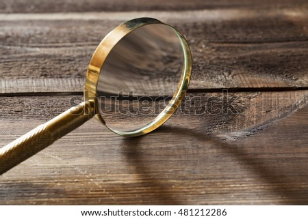 Gold magnifying glass with shadow on wooden background