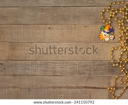 Gold Mardi Gras Beads with Court Jester on Rustic Brown Wood Background with room or space for copy, text, your words.  Above looking down horizontal - stock photo