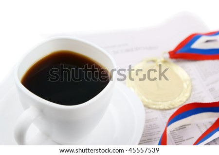 Gold medal and coffee cup on newspaper isolated, focus on cup - stock photo