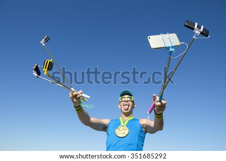 Gold medal athlete makes a face for his many gadgets on selfie sticks as he poses for a picture - stock photo