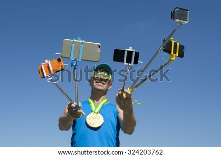 Gold medal athlete smiling for his many gadgets on selfie sticks as he poses for a picture - stock photo