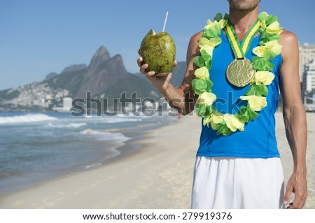 Gold medal athlete wearing gold medal celebrating with coconut on Ipanema Beach Rio de Janeiro Brazil  - stock photo