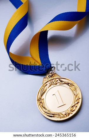 Gold medal in the foreground on yellow blue ribbon - stock photo