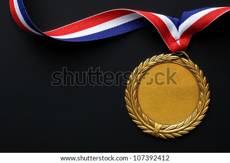 Gold medal on black with blank face for text, concept for winning or success - stock photo