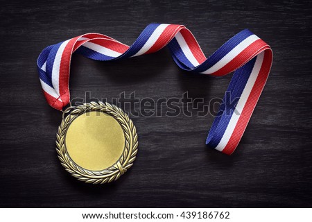 Gold medal on black wood background with blank face for text, concept for winning or success - stock photo