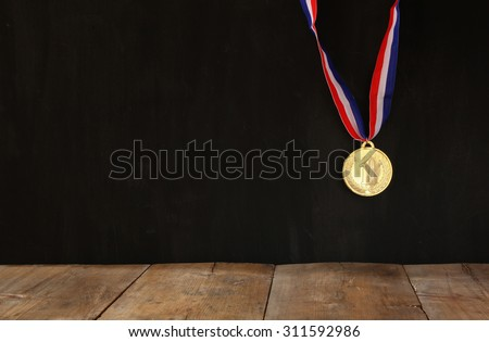 Gold medal over textured black background with room for text, winning and success concept - stock photo