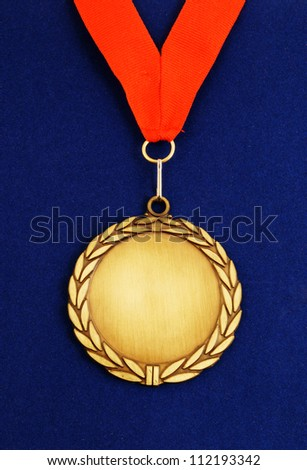 Gold medal with red ribbon on blue velveteen - stock photo